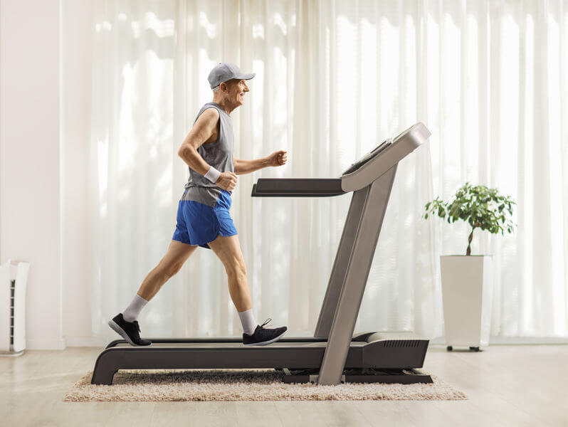 senior man walking on treadmill at home