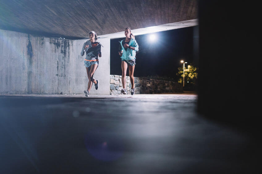 two female runners running together at night in city