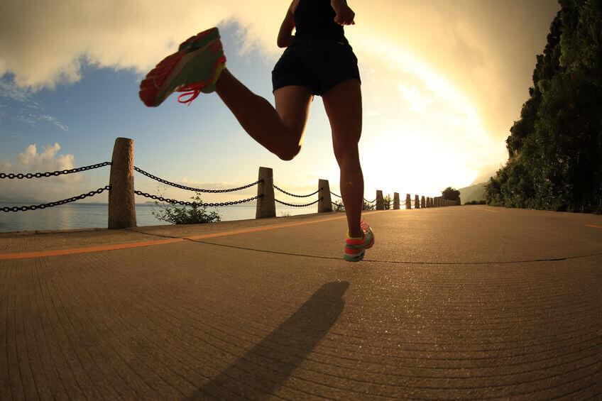 woman running on sunrise seaside trail